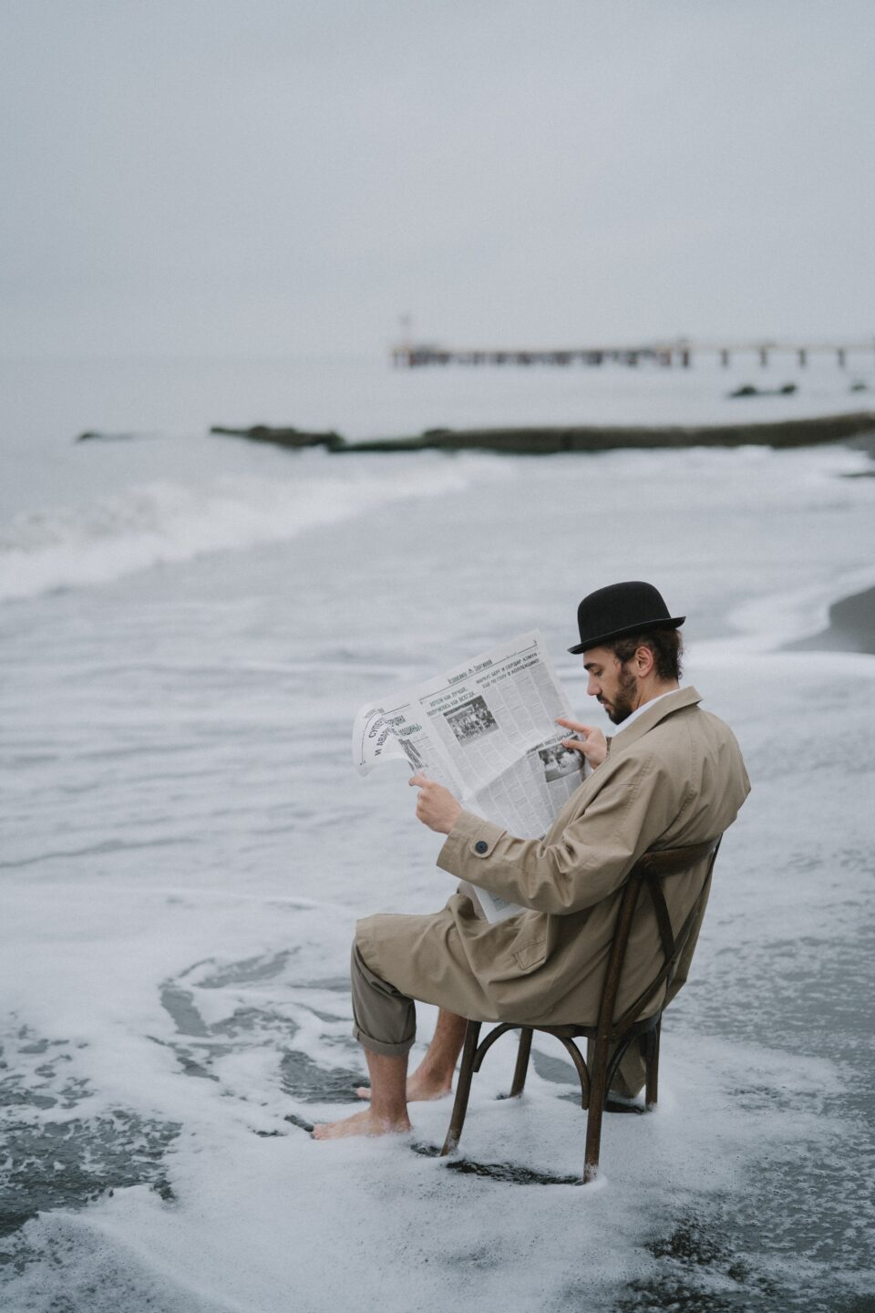 man reading newspaper at the beach